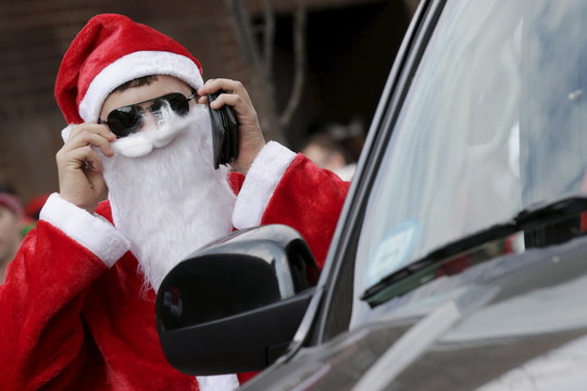 A man dressed as Santa Claus looks at himself in a car mirror during the annual SantaCon event in the Brooklyn borough of New York