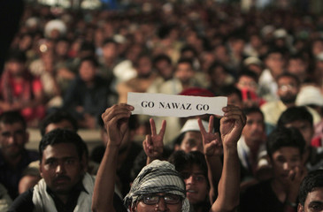 Man holds up an anti-government slogan written on a piece of paper while listening to a speech by Qadri, Sufi cleric and opposition leader of political party PAT, with others in front of Parliament house in the Red Zone during Revolution March in Islamabad