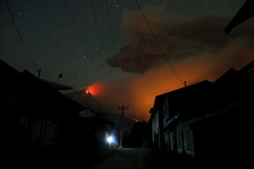 Mount Sinabung volcano spews hot lava as seen from an empty village inside the danger zone area at Beras Tepu Village in Karo Regency