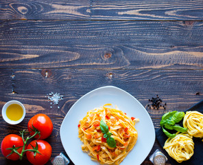 Tagliatelle with tomato and basil, made at home, on a wooden background.