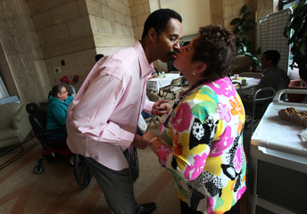 AIDS patient Campbell, 58, kisses a nurse as he arrives for a morning tea time at Broadway House for Continuing care in Newark