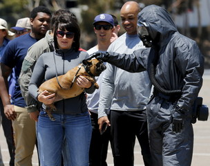 A first responder wearing a level 2 hazmat suit pats a dog as they prepare to scan volunteers for radiation exposure while training for a mass-casualty hazardous materials disaster in San Diego