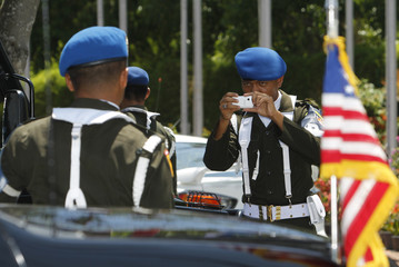An Indonesia police officer takes a picture of his colleague posing in front of the U.S. presidential car during the East Asia Summit in Nusa Dua, Bali