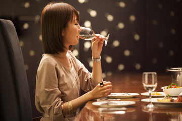 A young woman is drinking white wine at once