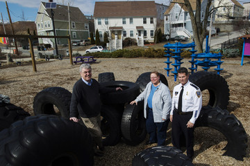 Shea of Olneyville Housing Corporation, Howard of Local Initiatives Support Corporation and Lieutenant Isabella of Providence Police Department pose for a photograph in Olneyville neighborhood of Providence, Rhode Island
