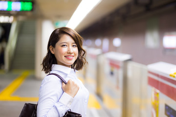 young woman waiting the subway on platform.