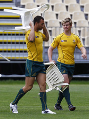Australia Wallabies' Quade Cooper carries a chair as he walks with teammate Berrick Barnes after an official team photograph at their Captain's run at North Harbour Stadium in Auckland