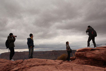 Tourists snap pictures from a spot overlooking the Grand Canyon and the Colorado River below, on the Hualapai Indian Reservation, Arizona