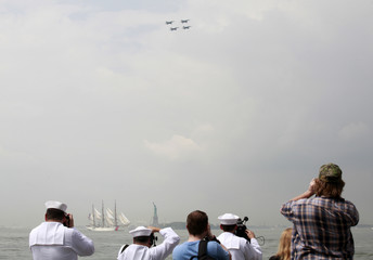 Members of the U.S. Navy take pictures of the United States Coast Guard cutter Eagle as it passes the Statue of Liberty in New York Harbor