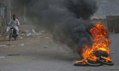 A man rides a motorcycle through the smoke of tyres burnt by angry protesters against target killing in Karachi