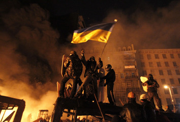 Anti-government protesters are seen at the site of clashes with riot police in Kiev