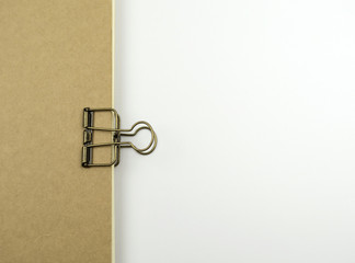 paper clip on brown notebook.