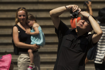 A man shields his eyes from the summer sunshine as he photographs on the street in New York