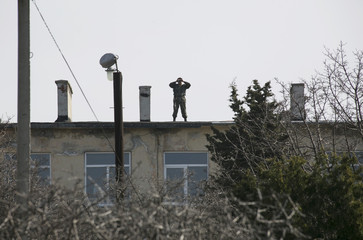 Ukrainian serviceman stands on roof of their base as uniformed men believed to be Russian servicemen stand guard at a Ukrainian military base near Sevastopol,
