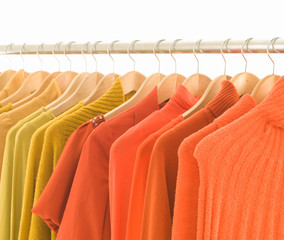 Variety of colorful female yellow and orange clothing on hanging