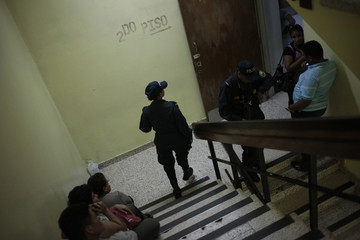 Honduran police officers patrol Hospital Escuela, where inmates affected during a massive fire at Comayagua jail are being treated at, in Tegucigalpa