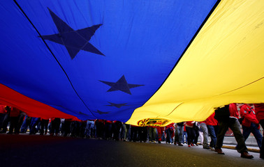 Workers of state-run oil company PDVSA holding a Venezuelan flag take part in a pro-government rally in Caracas