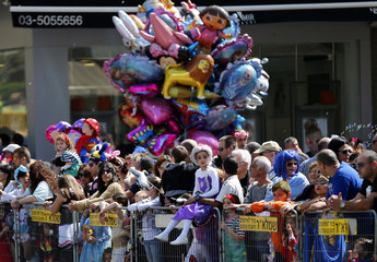 People dressed in costumes watch the annual parade marking Purim near Tel Aviv