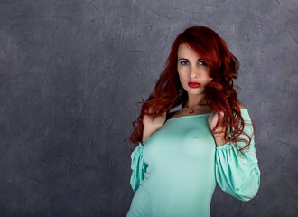 sexy beautiful redhead young woman with big boobs in a turquoise dress on a gray background