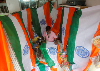 A worker stitches national flags at a workshop ahead of India's Independence Day celebrations in Agartala