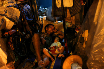 A man and his daughter sleep at the door of their house in Bangkok