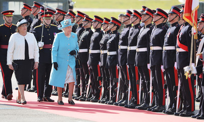 Queen Elizabeth II and the President of Malta Coleiro Preca inspect an honor guard before the Queen's departure from Luqa airport near Valletta