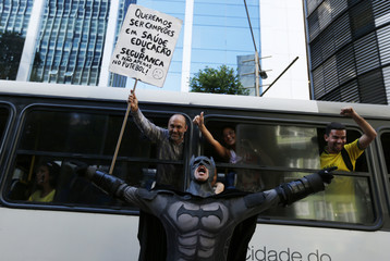 An anti-government demonstrator dressed as Batman yells slogans accompanied by passengers on a bus, during a protest against the 2014 World Cup in Rio de Janeiro