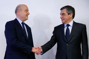 Francois Fillon, former French prime minister, and Alain Juppe, current mayor of Bordeaux, shake hands after the results in the second round for the French center-right presidential primary election in Paris