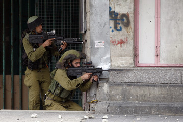 Israeli soldiers take position during clashes with stone-throwing Palestinians in Hebron