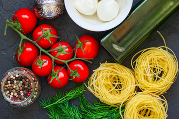 Ingredients for italian style dinner. Olive oil, dill, cherry tomatoes, spices, mozzarella and italian whole grain pasta on a black slate background. Top view.