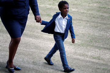 A child holds hands as he walks out of a sporting event with youth that Prince Harry attended during his official visit in St. Johns