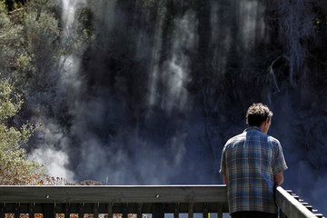 A tourist visits mud volcanoes and geysers at Wai-O-Tapu