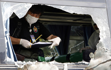 A member of the National Bureau of Investigation forensic team collects evidence as he examines a damaged passenger bus parked inside a police headquarters in Taguig city