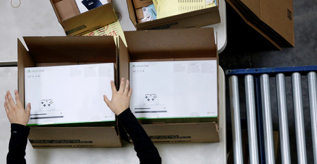 An employee boxes video gaming consoles at the Newegg warehouse on Cyber Monday in City of Industry
