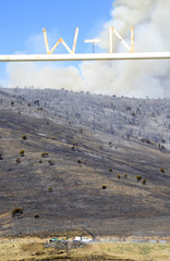 Fire crews watch for hot spots at ranch as Wood Hollow Fire burns in the background north of Fairview