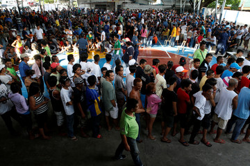 Residents, who admitted to be drug users, gather at a police camp, after more than 700 people surrendered to policemen and local government officials in Quezon city, Metro Manila