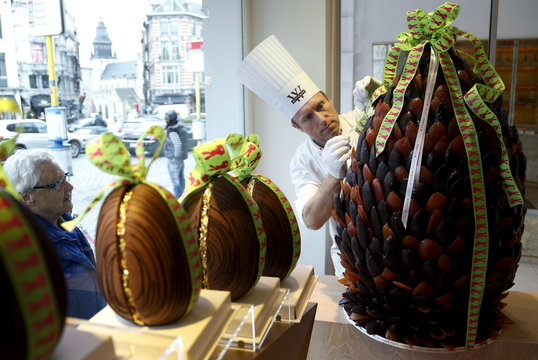 British pastry cook Lewis-Anderson adjusts a giant chocolate egg at a Wittamer chocolate boutique in Brussels