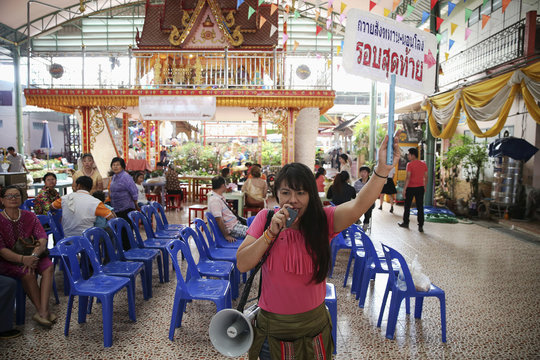 """A woman holds a sign reading """"Offering alms, Sleeping in coffins, Last round"""" as she invites people at Wat Takien temple in Nonthaburi province"""