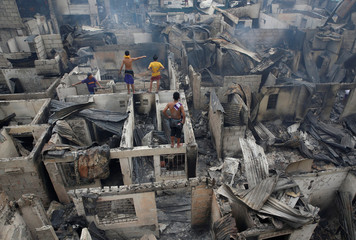 Residents stand on a burnt house after a fire in the residential district of Addition Hills in Mandaluyong, Metro Manila