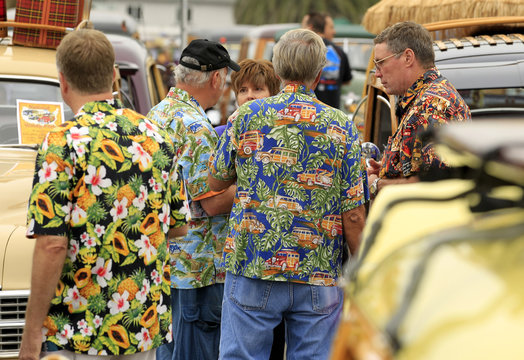 "Men in Hawaiian shirts gather around ""Woodie"" automobiles parked at the the world's largest gathering of wooden bodied automobiles in Encinitas"