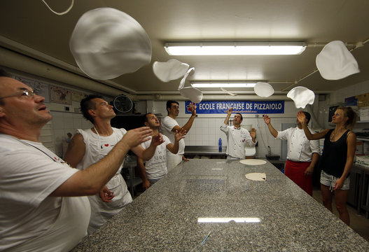 Adults throw pizza dough in the air as they practice during an acrobatic pizza course at the French pizzaiolo school, in Cap D'Ail