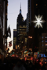 An illuminated snowflake hangs over 5th Avenue as the sun sets behind the Empire State Building in New York
