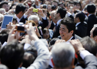 Japan's Prime Minister Shinzo Abe greets guests during a cherry blossom viewing party in Tokyo