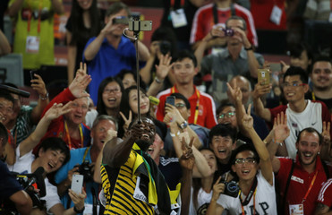 Usain Bolt of Jamaica takes a picture with fans after winning the men's 200 metres final during the 15th IAAF World Championships at the National Stadium in Beijing