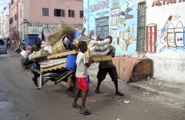Civilians push a cart loaded with their belongings as they flee from renewed clashes in Somalia's capital Mogadishu