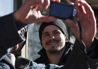 Actor Jason Ritter poses for a photo with a fan on Main Street during the Sundance Film Festival in Park City, Utah