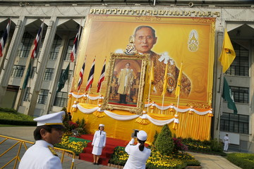 Army officials take pictures in front of Thai King Bhumibol Adulyadej portrait as people gather to mark his 88th birthday, in Bangkok