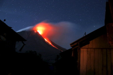 Mount Sinabung volcano spews lava as seen from an empty village inside the danger zone area at Beras Tepu Village in Karo Regency, Indonesia's North Sumatra province