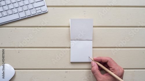 Wall mural workspace desk with keyboard  and hand write notebook background wood