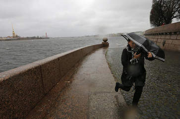 A woman with an umbrella walks opposite the Peter and Paul fortress during strong storm winds and rain in central St. Petersburg